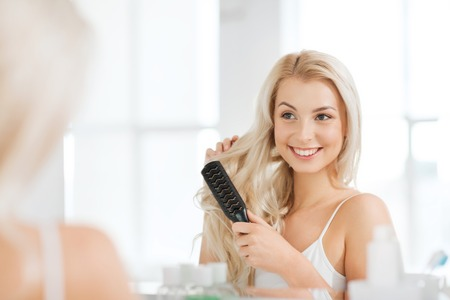 hair and beauty: beauty, grooming and people concept - smiling young woman looking to mirror and brushing hair with comb at home bathroom Stock Photo