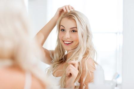 Schönheit, Hygiene, Frisur, morgens und Menschen Konzept - lächelnde junge Frau, die zu Hause Bad zu spiegeln Standard-Bild