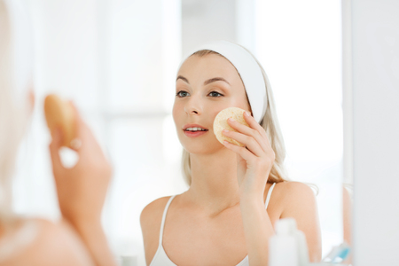 purifying: beauty, skin care and people concept - smiling young woman washing her face with facial cleansing sponge at bathroom