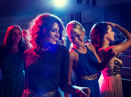 night out: party, holidays, celebration, nightlife and people concept - smiling friends dancing in club