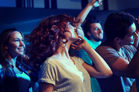 clubbers: party, holidays, nightlife and people concept - happy friends dancing at night club Stock Photo