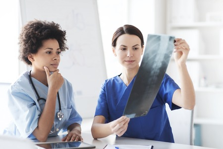 surgeons: radiology, surgery, people and medicine concept - female doctors looking to and discussing x-ray image at hospital