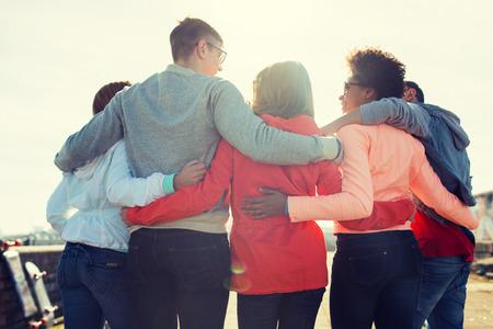 Tourismus, Reisen, Menschen, Freizeit und Teenager-Konzept - Gruppe von Freunden glücklich umarmt und sprechen auf Stadtstraße von der Rückseite Standard-Bild - 59328315