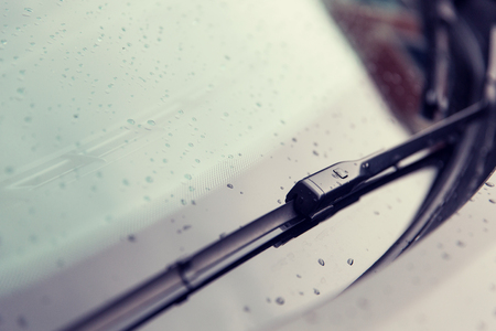 car glass: rainy weather and vehicles concept - close up of windshield wiper and wet car glass