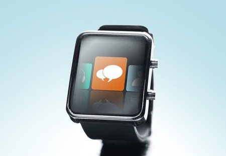 close icon: modern technology, communication, object and media concept - close up of black smart watch with text bubble icon on screen over blue background