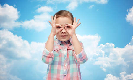 clouds making: childhood, fun, gesture and people concept - happy little girl making faces over blue sky and clouds background