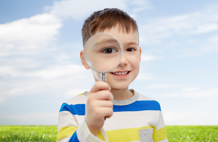 discoverer: childhood, investigation, discovery, vision and people concept - happy little boy looking through magnifying glass over blue sky and green field background