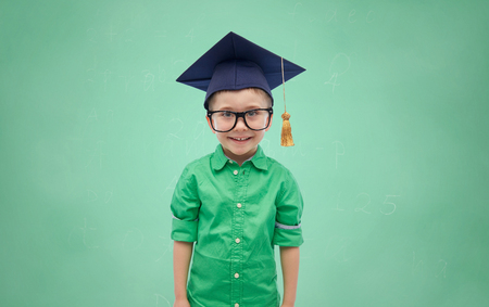 childhood, school, education, learning and people concept - happy boy in bachelor hat or mortarboard over green chalk board background