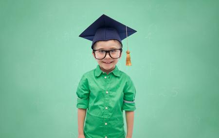 niño escuela: la infancia, la escuela, la educación, el aprendizaje y el concepto de la gente - muchacho feliz en el sombrero de licenciatura o birrete sobre el fondo pizarra verde Foto de archivo