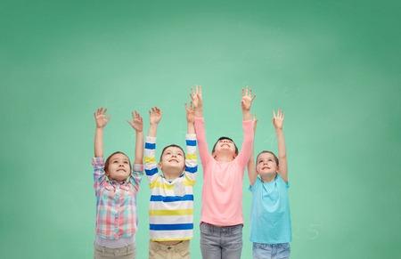 niños estudiando: la infancia, la escuela, la educación, el gesto y el concepto de la gente - felices los niños sonrientes que levantan las manos y celebran la victoria sobre la escuela verde fondo de la tarjeta de tiza