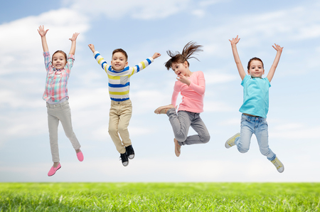 air movement: happiness, childhood, freedom, movement and people concept - happy little children jumping in air over blue sky and grass background Stock Photo