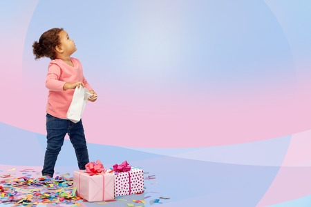 advertising space: childhood, birthday, party, holidays and people concept - happy little african american baby girl with gift boxes and confetti playing with shopping bag looking up over pink and violet background