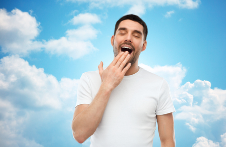 bedtime: rest, bedtime and people concept - tired yawning man over blue sky and clouds background