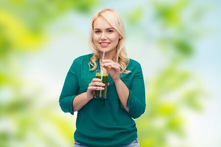 green vegetable: healthy eating, vegetarian food, diet, detox and people concept - smiling young woman drinking green vegetable juice or smoothie from glass over green natural background