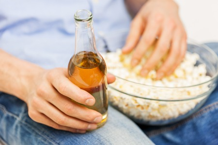 junkfood: food, junk-food, unhealthy eating and people concept - close up of man with popcorn and beer bottle at home