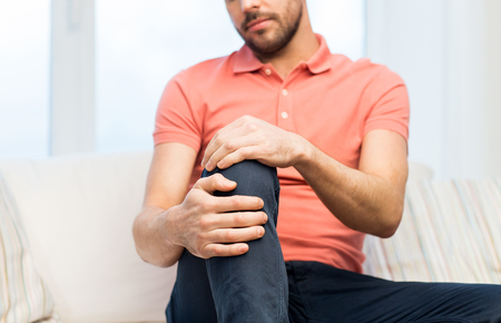 people, healthcare and problem concept - close up of young man suffering from pain in leg or knee at home Stock Photo