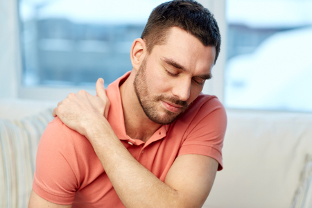 shoulder problem: people, healthcare and problem concept - unhappy man suffering from neck or shoulder pain at home