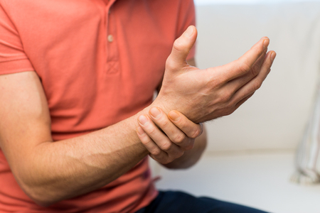 люди, здравоохранение и проблема концепция - крупный план человека, страдающий от боли в руке запястье у ого дома Фото со стока