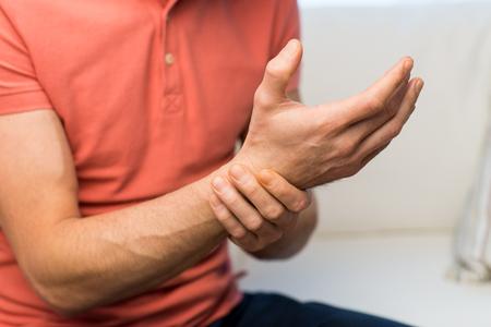 dolor: las personas, la salud y el problema de concepto - cerca del hombre que sufre de dolor en la mano oe la muñeca en el hogar