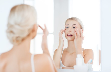 eye cream: beauty, skin care and people concept - smiling young woman applying cream to face and looking to mirror at home bathroom