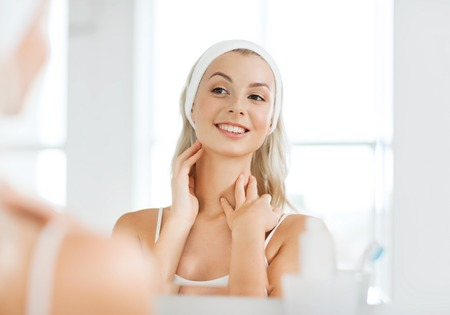 woman neck: beauty, skin care and people concept - smiling young woman in hairband touching her face and looking to mirror at home bathroom