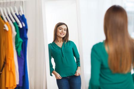 ropa, moda, estilo y concepto de la gente - la mujer feliz elige la ropa y que presenta en el espejo en el armario de su casa