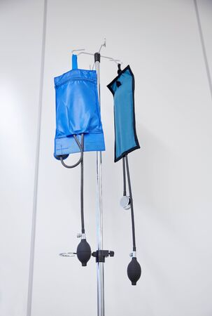 cuffs: medicine, health care and medical equipment concept - two sphygmomanometers or pressure infusion cuffs hanging on holder at hospital Stock Photo
