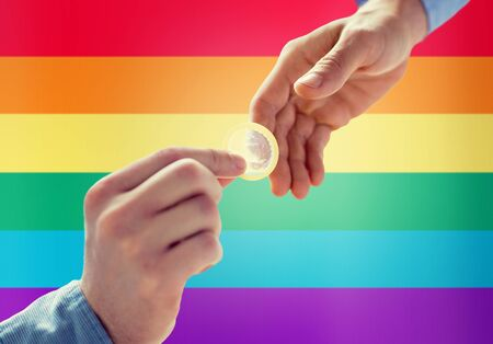 educacion sexual: people, homosexuality, safe sex, sexual education and charity concept - close up of happy male gay couple hands giving condom over rainbow flag background