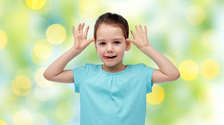 fun background: childhood, fashion, fun and people concept - happy little girl having fun and making ears over summer green lights background Stock Photo