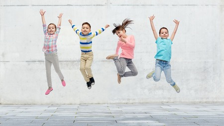 happiness, childhood, freedom, movement and people concept - happy little girl jumping in air over concrete wall on street background Stock Photo