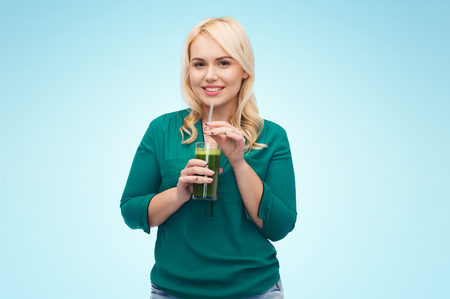 green vegetable: healthy eating, vegetarian food, diet, detox and people concept - smiling young woman drinking green vegetable juice or smoothie from glass over blue background