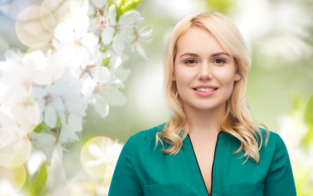brown eyes: spring and people concept - smiling young woman face over natural cherry blossom background