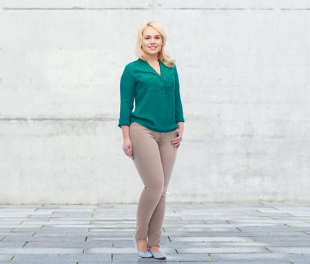 edad de piedra: femenino, género, retrato, más el tamaño y el concepto de la gente - mujer joven y sonriente en camisa y pantalones sobre el fondo de hormigón urbano Foto de archivo