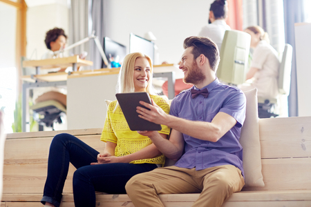 negocios, tecnología, puesta en marcha y el concepto de la gente - equipo creativo feliz con el ordenador Tablet PC en la oficina Foto de archivo