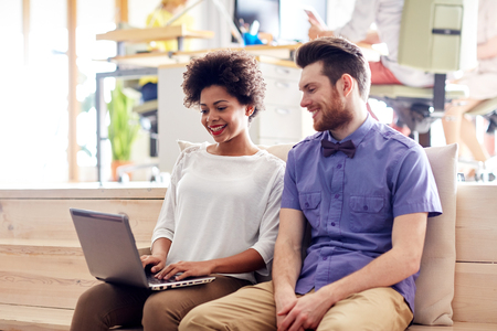 african american woman business: business, startup and people concept - happy creative team with laptop computer and folder in office