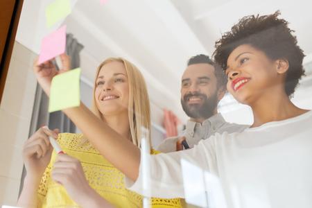 ビジネス、スタートアップ、プランニング、管理、人々 のコンセプト - 事務所ガラス板でステッカーに書いて幸せ国際創造的なチーム