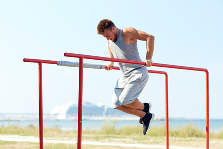 calisthenics: fitness, sport, exercising, training and lifestyle concept - young man doing triceps dip on parallel bars outdoors Stock Photo