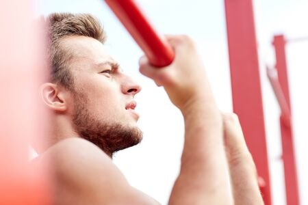 gripping bars: fitness, sport, exercising, training and lifestyle concept - young man doing pull ups on horizontal bar outdoors