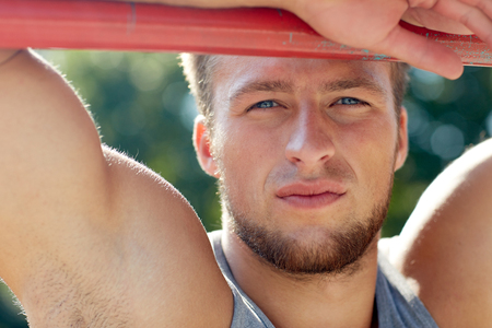 and the horizontal man: fitness, sport, training and lifestyle concept - young man exercising on horizontal bar outdoors