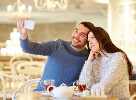 drinking tea: people, technology and dating concept - happy couple taking smartphone selfie and drinking tea at cafe or restaurant
