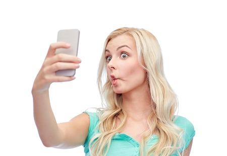 face expressions: expressions, technology and people concept - funny young woman or teenage girl taking selfie with smartphone and making fish face
