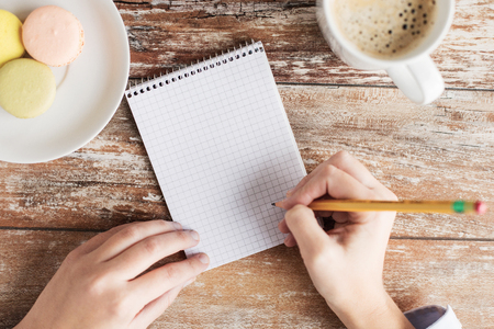 body writing: business, education and people concept - close up of female hands with with notebook, pencil, coffee and cookies on table
