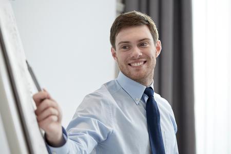 concept d'affaires et de personnes - souriant marqueur de pointage homme d'affaires à flipboard sur présentation au bureau Banque d'images