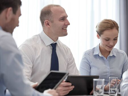 business conference: business, conference, people, technology and teamwork concept - smiling businessmen and businesswoman with tablet pc computer meeting in office Stock Photo