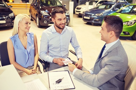 eur: auto business, sale and people concept - happy couple with dealer buying car in auto show or salon