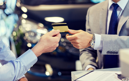 service card: auto business, sale and people concept - close up of customer giving credit card to car dealer in auto show or salon