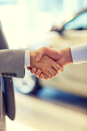 deal in: auto business, car sale, deal, gesture and people concept - close up of male handshake in auto show or salon Stock Photo