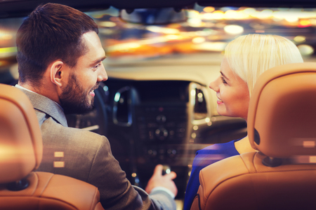 night lights: love, luxury, nightlife, automobile  and people concept - happy couple driving in cabriolet car over night city lights background