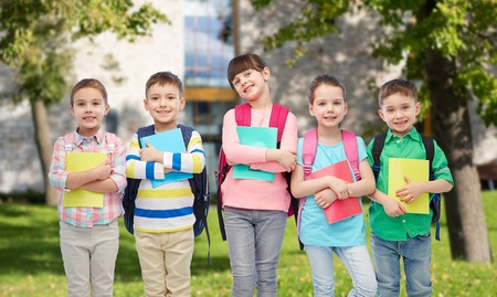 school bags: childhood, preschool education, learning and people concept - group of happy smiling little children with school bags and notebooks over summer campus background
