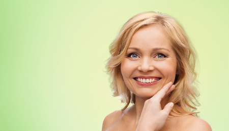 touching face: beauty, people and skincare concept - smiling woman with bare shoulders touching face over green natural background